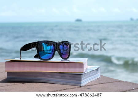 Sunglasses with shadow at lens and books on the floor with blur background of blue sea sky and mountains at day time.