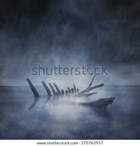 Sunken boat remains protrude from the sand in a dark, lonely, moonlit seascape captured using long exposure, bokeh and other effects with some areas blurred to create a surreal and dreamlike effect.
