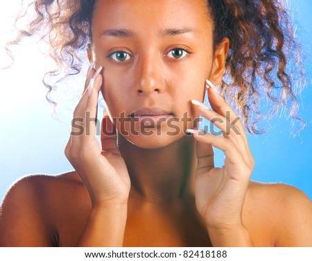 sunny beautiful woman with is touching her face and looking at camera on sky background