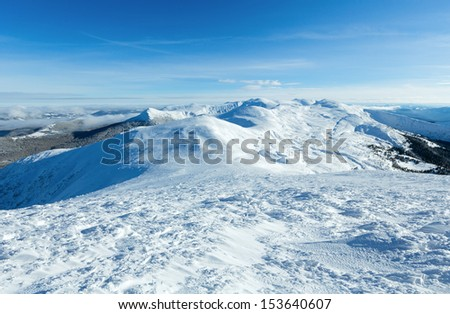 Sunny winter mountain landscape with low-hanging clouds and snowy ridge. (Chornohora , Carpathian, Ukraine).