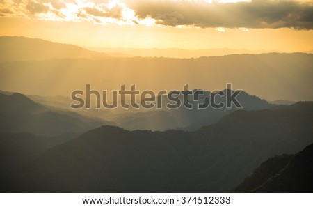 Sunset and foggy mountain valley landscape.