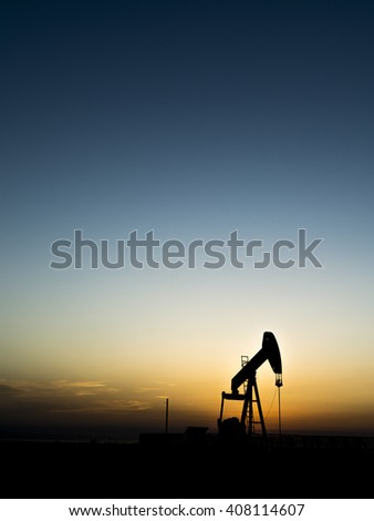 Sunset and silhouette of crude oil pump in oilfield