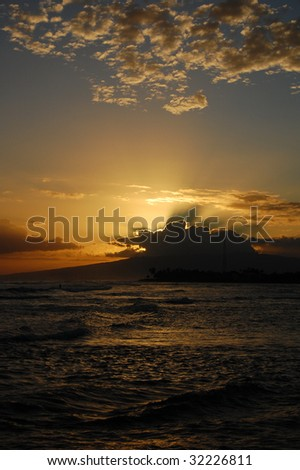 Sunset at ala moana beach hawaii. The sun was trying to shine behind the big nice cloud creating a wonderful, powerful beam coming out from the thick sky