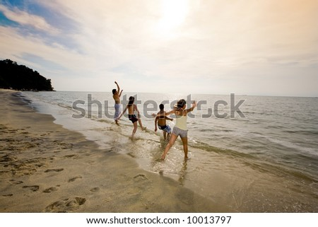 sunset beach with a group of friends having fun jumping