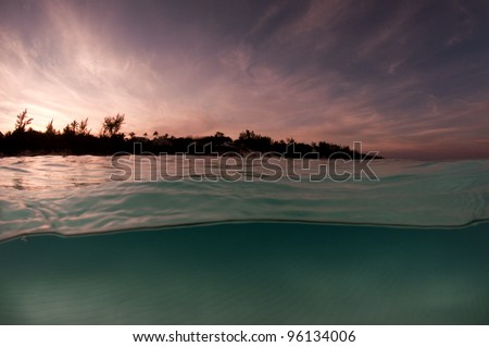 sunset behind an island with half above and half under water