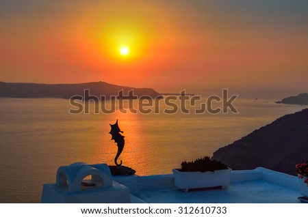 Sunset behind the hippocampus figure in Santorini island