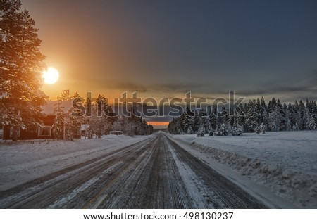 Sunset over scenic road in a typical village of Lapland Finland