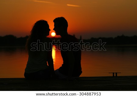 Sunset silhouette. Young couple sitting on lake pier and kissing.
