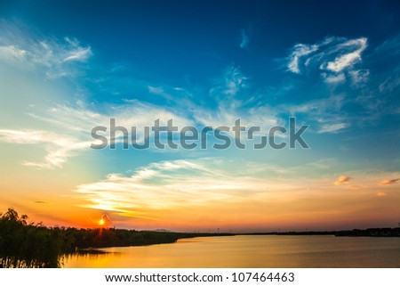 sunset with colorful sky near a urban lake