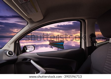 Sunset with reflections in the lagoon viewed from inside a car