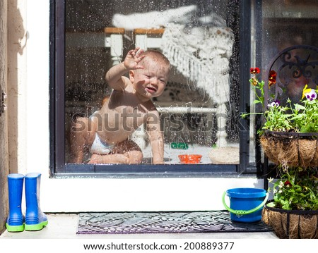 Sunshine after the rain - cute baby behind the glass doors