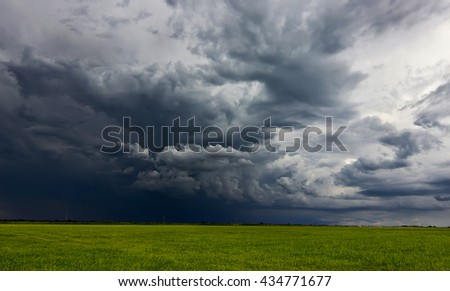 Supercell storm clouds above meadow with green grass Summer Storm clouds above meadow with green grass Rising Thunderstorm, Dramatic sky before storm. Dark clouds