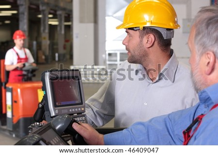 supervisor talking to forklift operator in warehouse