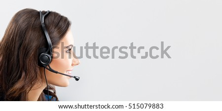 Support phone operator in headset, over grey background, with blank copyspace area for advertising slogan or text message. Caucasian brunette model in help servise and client consulting concept.