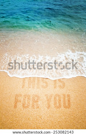 Surf wave on a inscription This Is For You on a sea beach