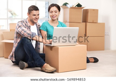 Surfing the net together. Cheerful young couple sitting on the floor and working on laptop while cardboard boxes laying on the background