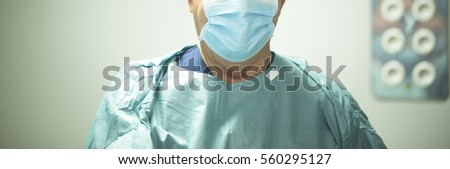 "Surgeon in hospital surgery in sterile uniform ""scrubs"" in operating theater emergency room in surgical operation."