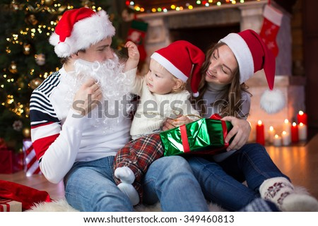 Surprised child boy looks at dad weared Santa Claus with fake beard sitting opposite Christmas tree