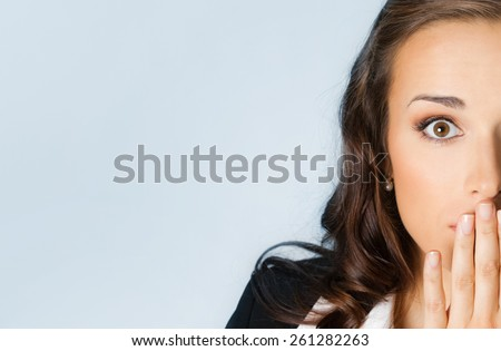 Surprised excited young businesswoman covering with hands her mouth, against blue background