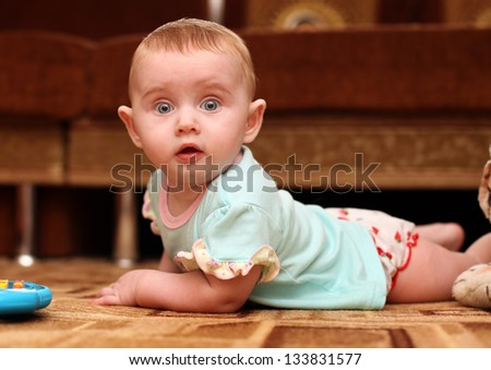 Surprised Little Baby on the Floor in Home Interior