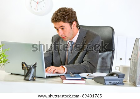 Surprised modern businessman looking in laptop at office