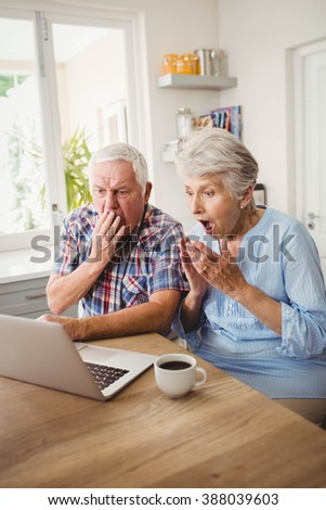 Surprised senior couple using laptop at home