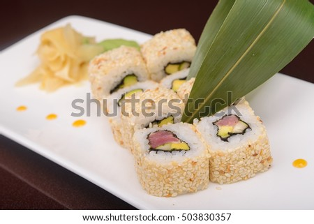 Sushi rolls on a white plate,  japanese food, glass dark background