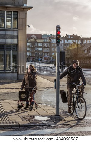 Sweden, Malmo. 9 december 2016. Crossroad, two people are waiting for the green light, man on bicycle, woman with bag on wheels.