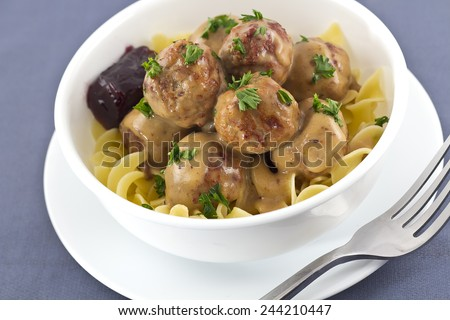 Swedish meatballs in creamy gravy with curly egg noodles and grape jelly