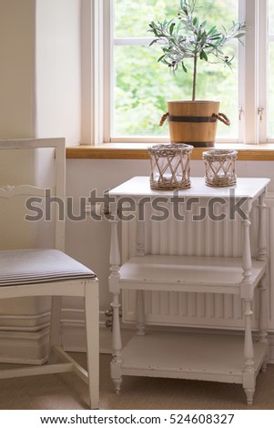 Swedish style interior design. Vintage white painted chair with blue and white striped cushion and table by a sunny window. A small potted olive tree sits on the window sill.