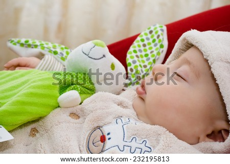 Sweet baby sleeping with stuffed rabbit