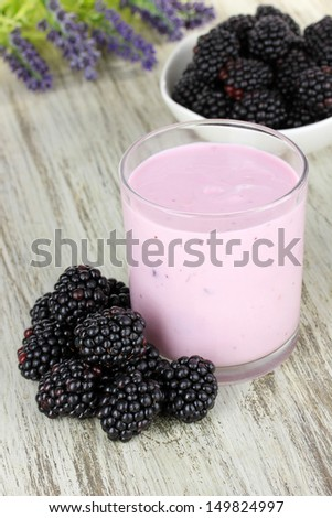 Sweet blackberries with yogurt on table close-up