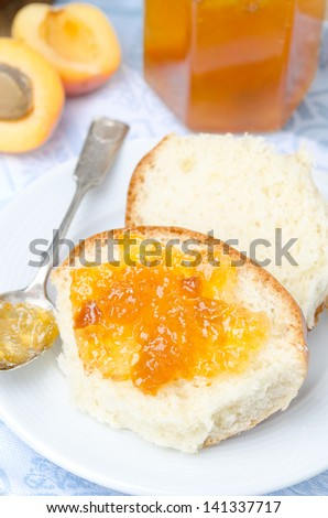 Sweet bun with apricot jam on the plate for breakfast, vertical