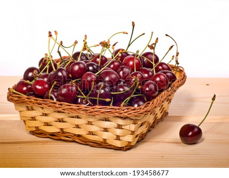 sweet cherries in basket on wooden table