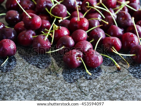 Sweet cherries on dark granite background