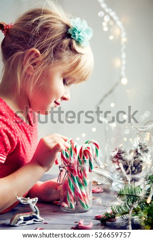 Sweet Christmas: little girl playing with xmas decorations and candies, closeup shot