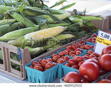 Sweet corn, one ear partially peeled, and grape tomatoes in containers for sale at an outdoor farmers market