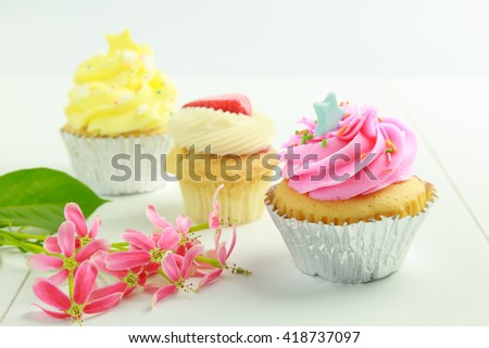 Sweet cupcakes with pink flowers on white table