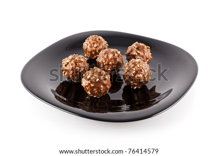 Sweet, delicious, big chocolate balls filled with hazelnuts and flips on the black plate and white background.