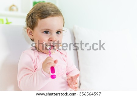 Sweet little baby girl eating her first cake on the sofa.Copy space, shallow doff