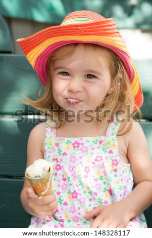 Sweet little blond girl in a straw hat eating her ice cream in the summer sunshine