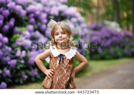 Sweet little girl with crown, outdoor photo. Soft focus.