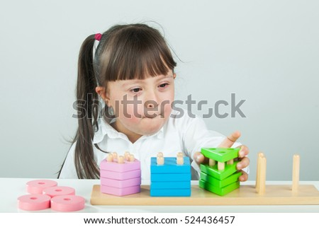 Sweet little girl with Down Syndrome, playing with wooden toys