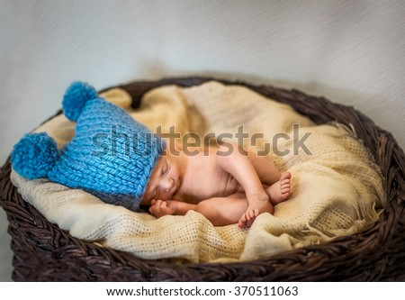 sweet newborn baby sleeping alone in a blue knitted hat