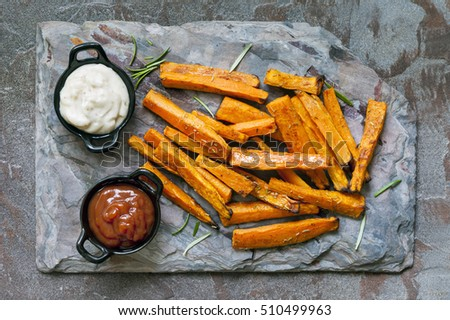Sweet potato fries on slate.  Top view, with ketchup and mayonnaise.