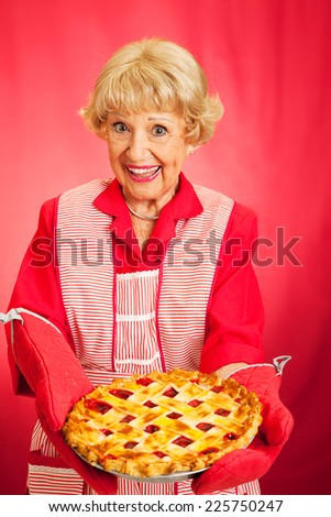 Sweet retro grandmother holding a beautiful homemade cherry pie.