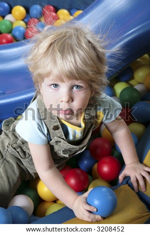 Sweet shaggy blond boy playing with balls in special area