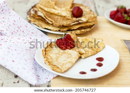 Sweet thin french style crepes served with strawberries