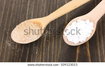 Sweetener and brown sugar in spoons on wooden background