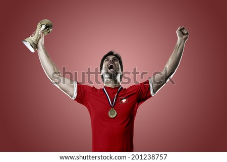 Swiss soccer player, celebrating the championship with a trophy in his hand. On a red background.